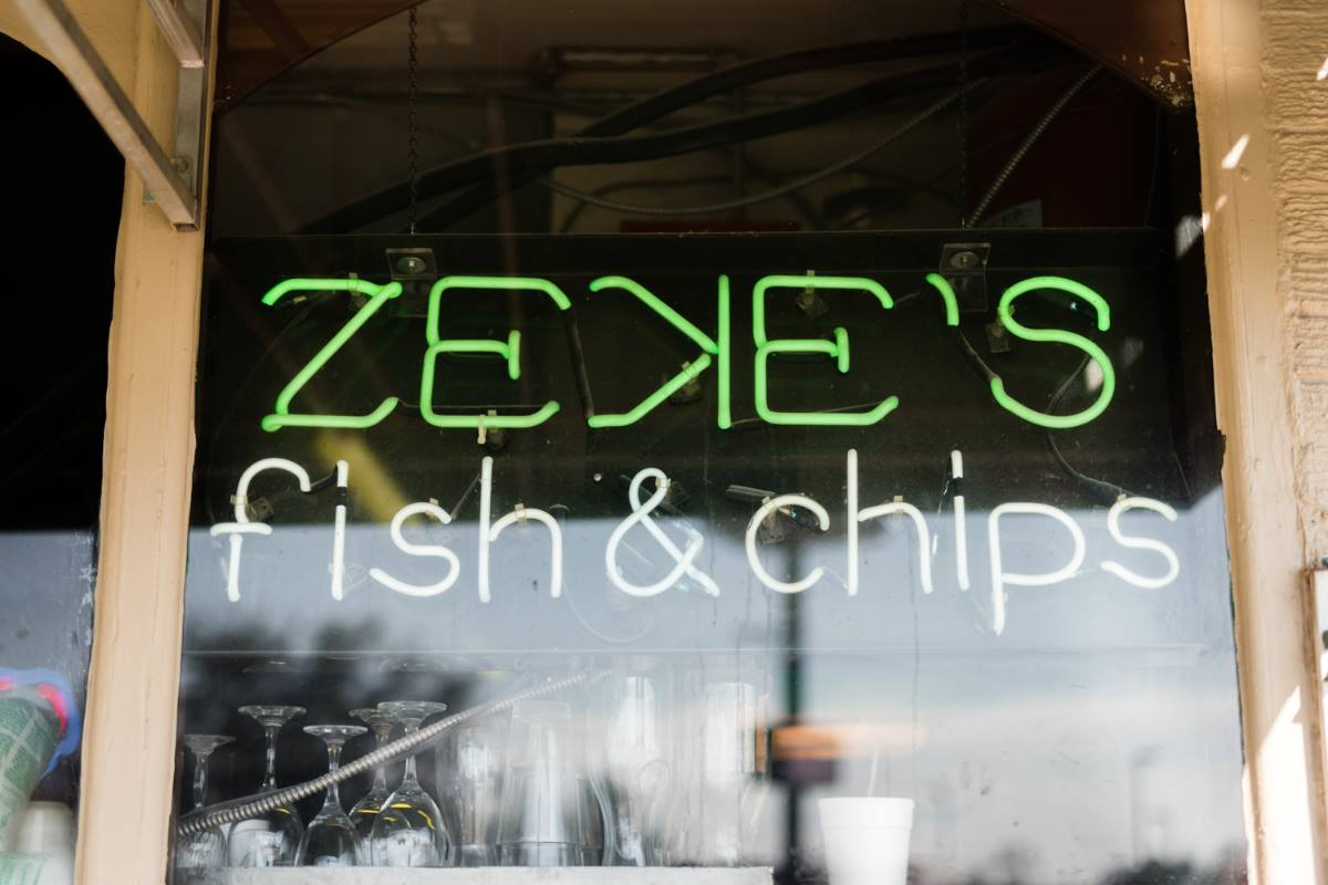 A storefront sign for Zeke's Fish & Chips